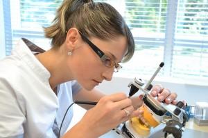 Eine Zahntechnikerin der Dentaprime-Zahnklinik arbeitet an einem eingestellten Artikulator