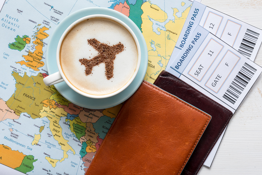 Aircraft made ofcinnamon in cappuccino, passports and boarding passes with Europe map. Travel concept